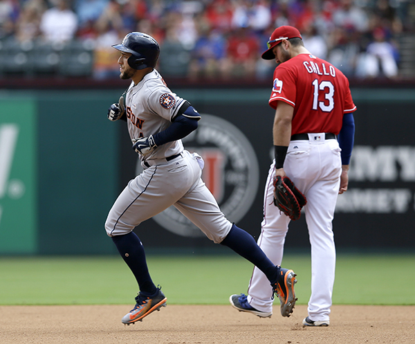 Houston Astros' George Springer, front, rounds the bases. The shot that came off of Rangers starting pitcher Martin Perez was the second of the game for Springer. (AP Photo/Tony Gutierrez)