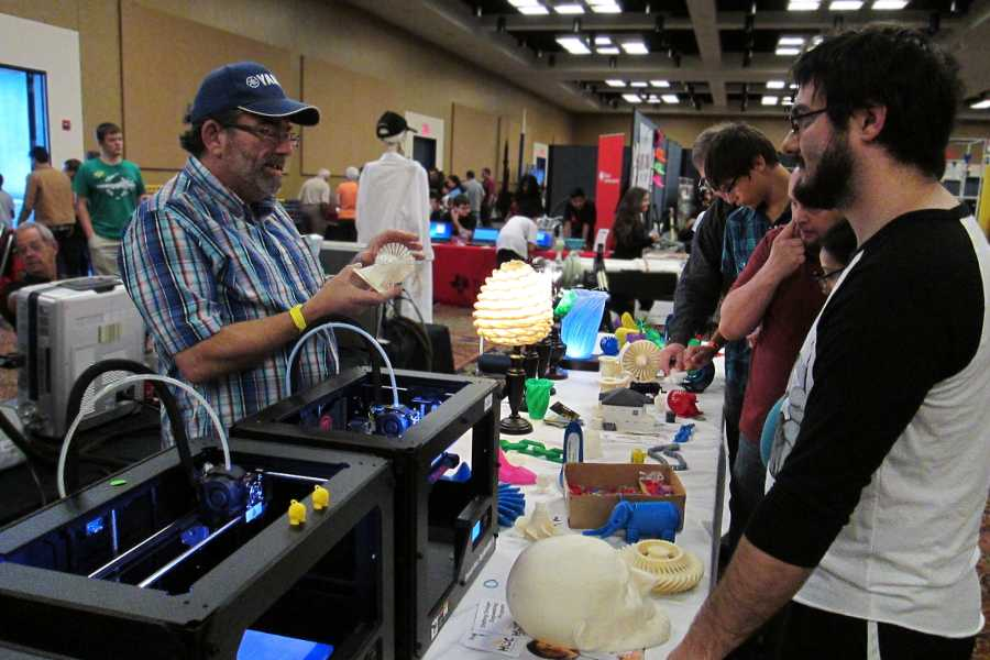 HCCs 3D Printing Table at Houston Mini Maker Faire 2014. Two MakerBots are printing trinkets in the foreground. On the table is dozens of 3D printed items.