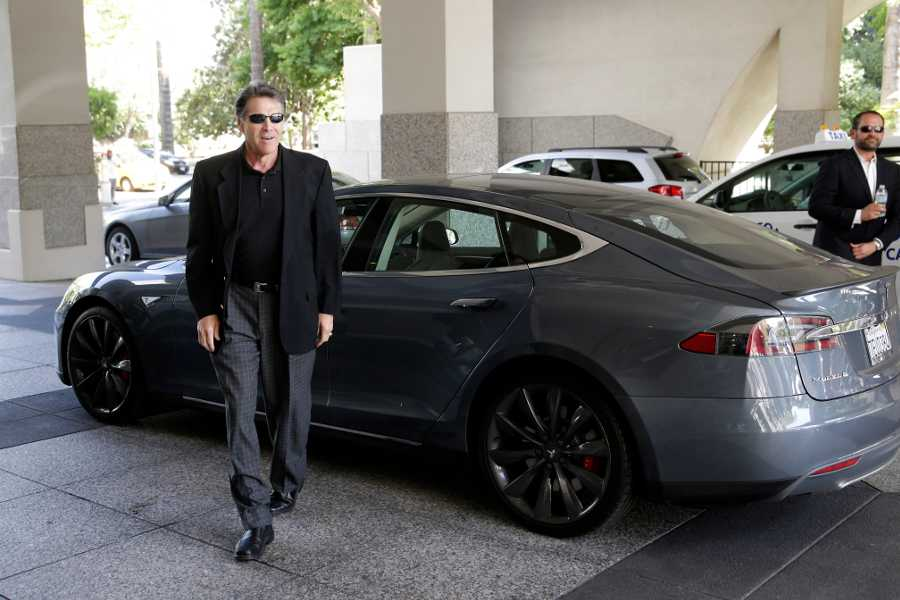In this photo from June 10, 2014, Texas Gov. Rick Perry walks over to talk to reporters after driving up in a Tesla Motors Type S electric car in Sacramento, Calif. Tesla passed on Texas as the site of its new $5 billion battery factory. But the automaker still hopes to sell its electric cars directly to Texans over the Internet, instead of through dealerships, and it is dangling the carrot of future investment projects as an incentive.