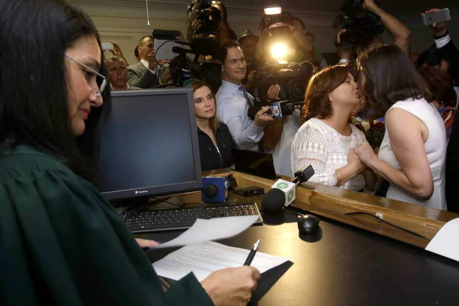 Catherina Pareto, right, and Karla Arguello, second from right, kiss after they were married by Circuit Court Judge Sarah Zabel, left, Jan. 5, in Miami. Zabel provided a jump-start Monday to Florida's entry as the 36th state where gays and lesbians can legally marry, saying she saw no reason why same-sex couples couldn't immediately get their licenses in Miami-Dade County ahead of a midnight launch statewide.