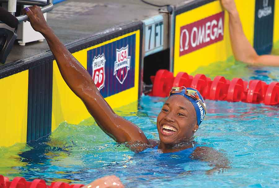 Simone Manuel smiles after winning the women's 50-meter freestyle final at the U.S. nationals of swimming in Irvine, Calif. Ryan and Simone Manuel were always close. They still talk just about every day, even though they attend college in different parts of the country.