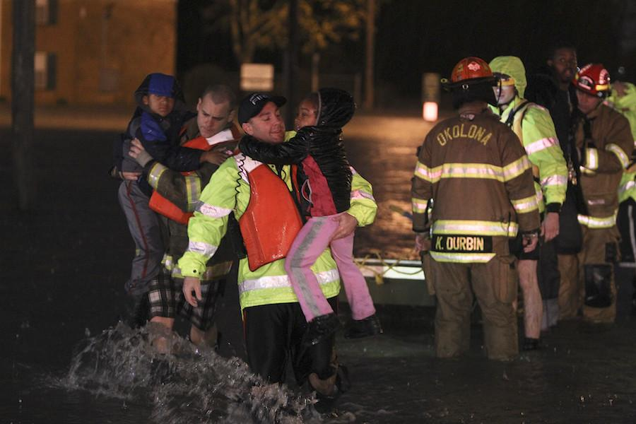Rescue crews help residents at the Guardian Court Apartments evacuate after flooding in the area on Friday, April 3, 2015 in Louisville, Ky.   Authorities in Louisville made more than 100 water rescues early Friday as area storms flooded roads and prompted at least one evacuation.