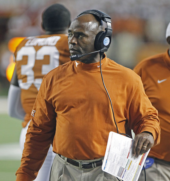 "In this Oct. 18, 2014, file photo, Texas head coach Charlie Strong watches from the sideline during  an NCAA college football game against Iowa State in Austin, Texas. The $600,000 question at Texas is just who calls the plays for the Longhorns' anemic offense. Assistant head coach Shawn Watson says he does. Offensive coordinator Joe Wickline says he does too. In fact, they swear they share. And head coach Charlie Strong? Well, he says they both do, ""And I'm on the headset."""