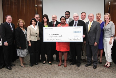 Katy Rotary Fund President Ken Burton (holding check on right) presented the organization's $30 thousand gift to The HCC Foundation at the HCC Board of Trustees meeting on Aug. 20. Here, members of the Katy Rotary stand with HCC Trustees, HCC's Chancellor and members of the HCC Foundation.
