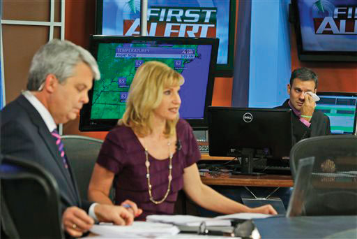 WDBJ-TV7 meteorologist Leo Hirsbrunner, right, wipes his eyes during the early morning newscast as anchors Kimberly McBroom, center, and guest anchor Steve Grant deliver the news at the station in Roanoke, Va., Thursday, Aug. 27, 2015. Reporter Alison Parker and cameraman Adam Ward were killed during a live broadcast Wednesday, while on assignment in Moneta.