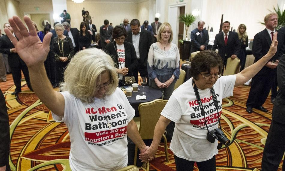 Rita Palomarez, left, and Linda Rodriguez pray during an election watch party attended by opponents of the Houston Equal Rights Ordinance on Tuesday, Nov. 3, in Houston. The ordinance that would have established nondiscrimination protections for gay and transgender people in Houston did not pass.