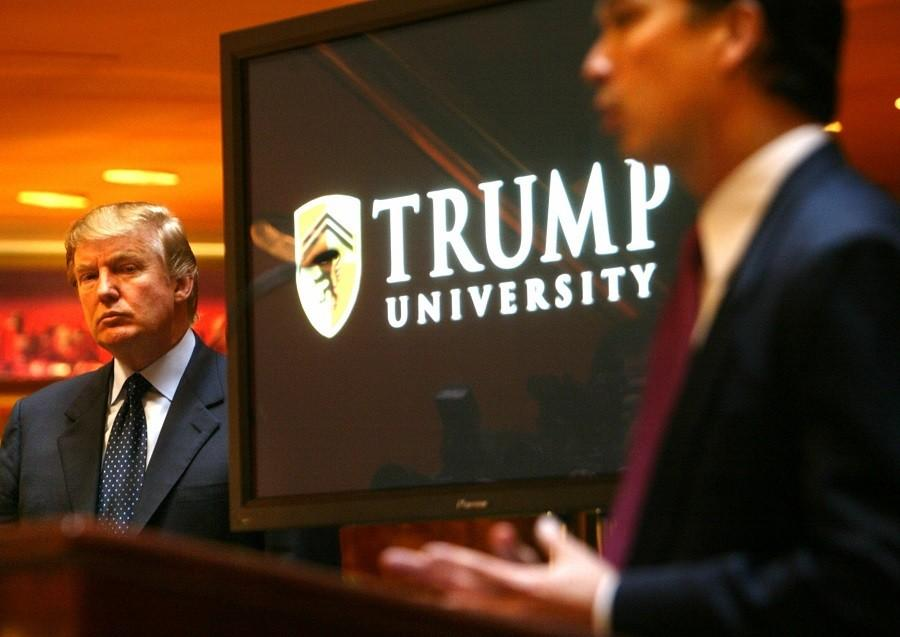 In this May 23, 2005 file photo, Donald Trump, left, listens as Michael Sexton, president and co-founder of the business education company, introduces him to announce the establishment of Trump University at a press conference in New York.  (AP Photo/Bebeto Matthews)