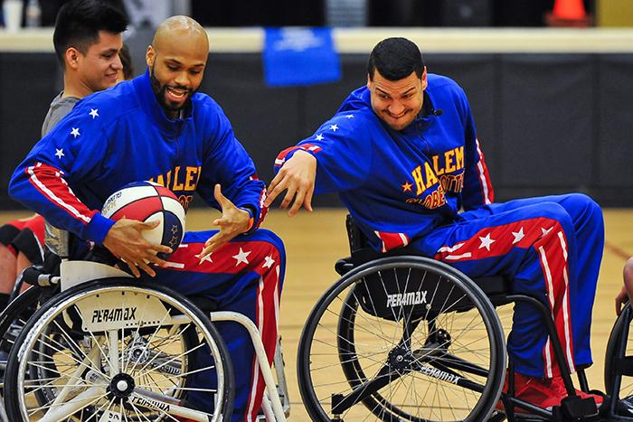 Globetrotter's El Gato and Hawk attempt to control the ball well trying to navigate their wheelchairs.