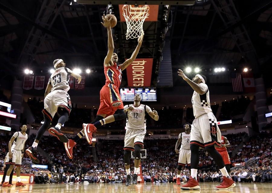 New Orleans Pelicans' Alexis Ajinca (42) goes up for a shot as Houston Rockets' Corey Brewer (33), Dwight Howard (12) and Josh Smith, right, defend during the second half of an NBA basketball game Wednesday, March 2, 2016, in Houston. The Rockets won 100-95. (AP Photo/David J. Phillip)