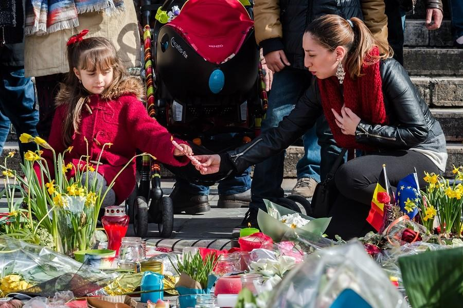 A woman and a girl light candles at floral tributes at a memorial site at the Place de la Bourse in Brussels, Saturday, March 26, 2016.