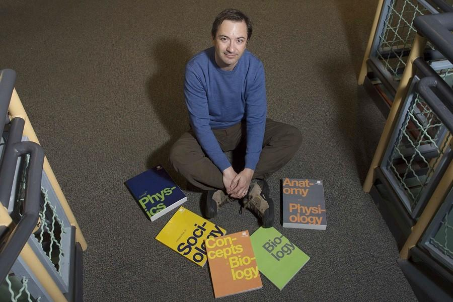 Richard Baranick, Director of OpenStax, sits among five of many college textbooks which are available through the program.