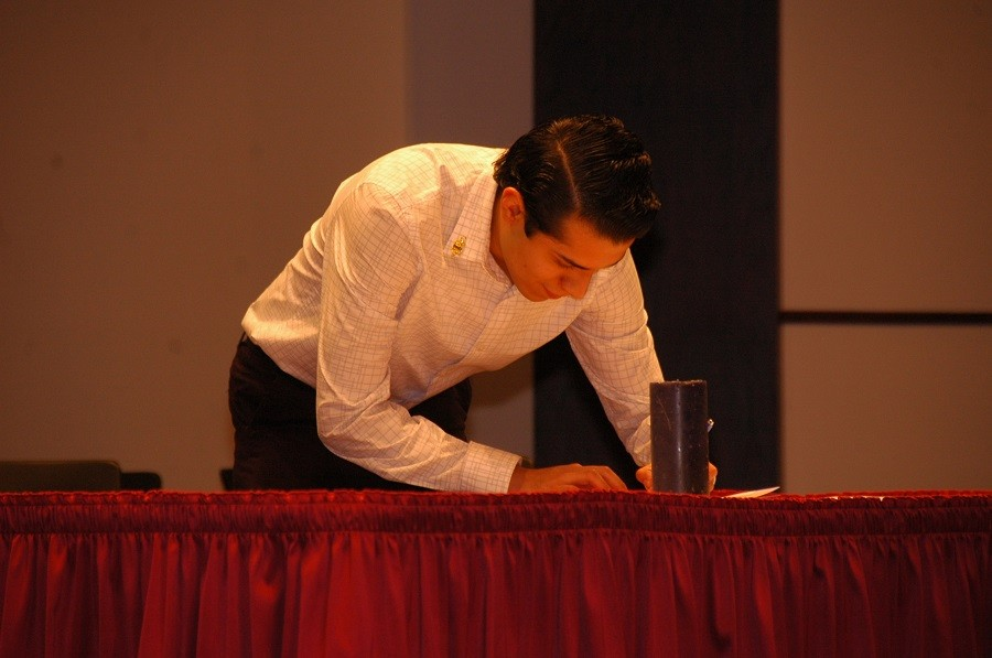 A new Phi Theta Kappa member signs the official membership record at the society's spring induction ceremony on April 1.
