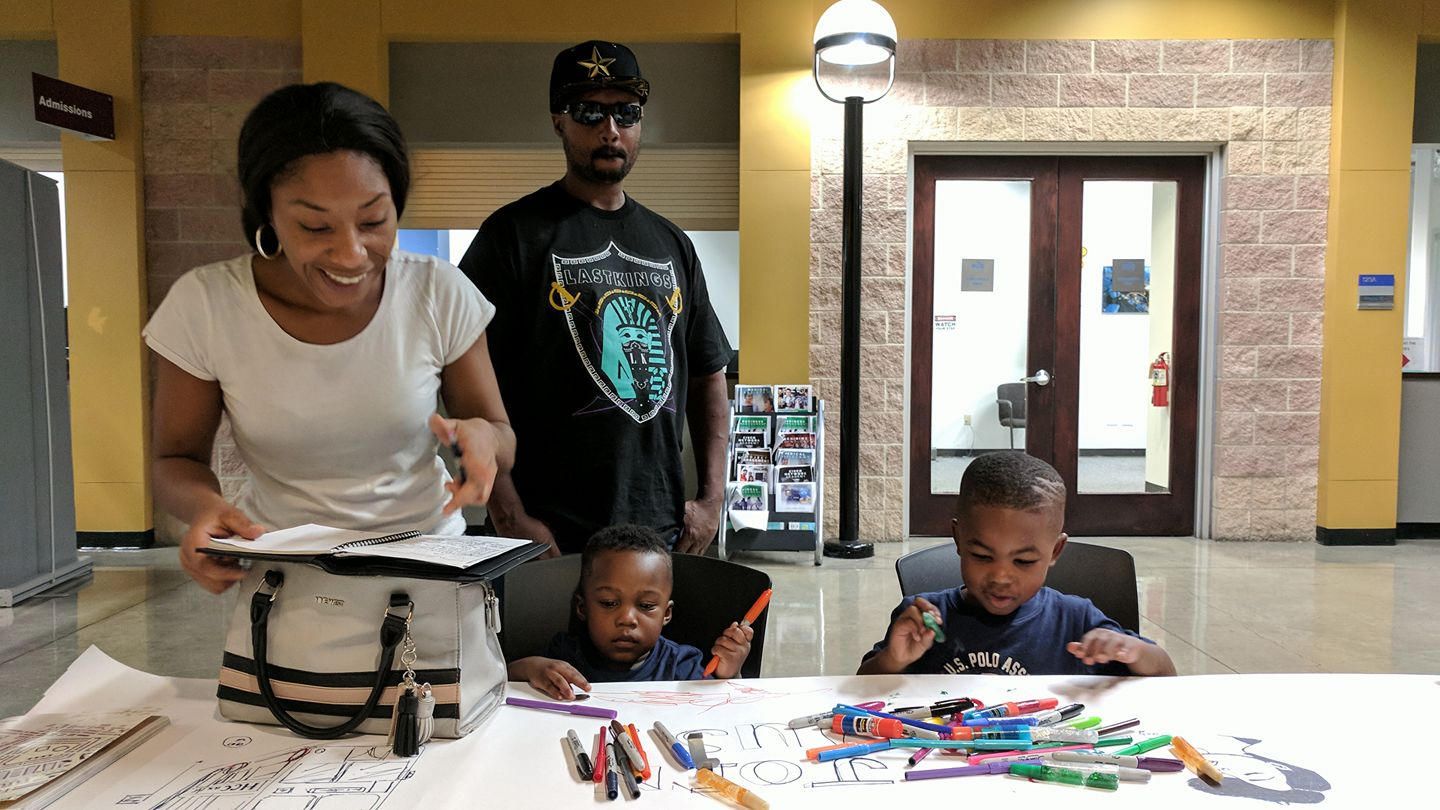 Kiara Murphy and Arindell Hodge with their sons Jerry and Jace draw at the table.