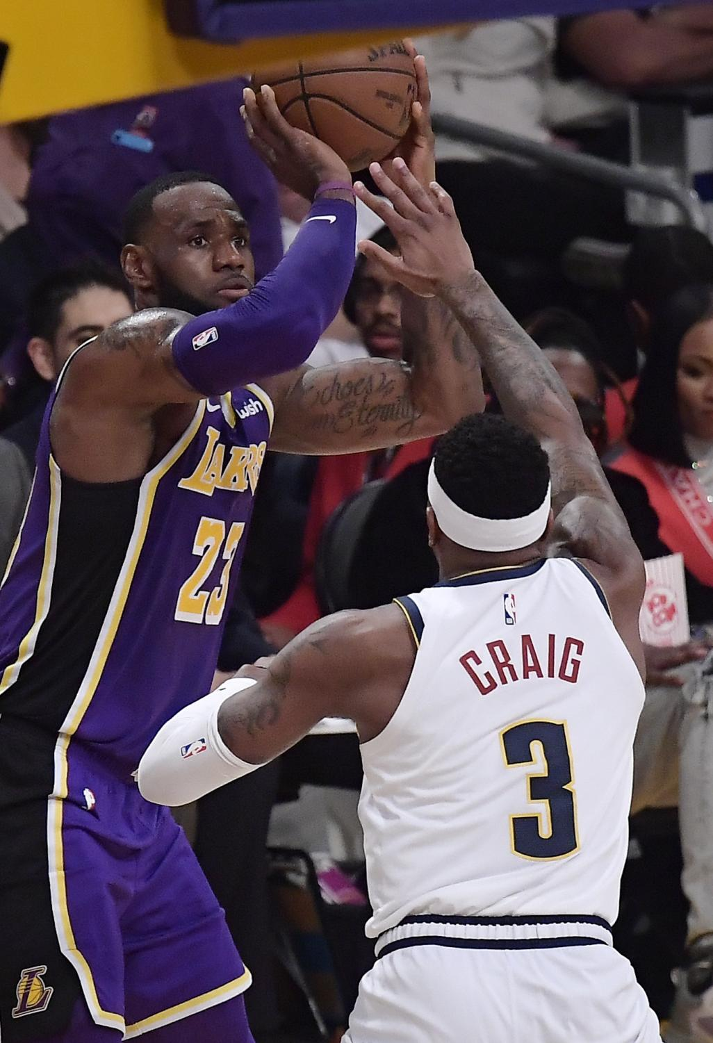 Los Angeles Lakers forward LeBron James, left, shoots and scores as Denver Nuggets forward Torrey Craig defends during the first half of an NBA basketball game Wednesday, March 6, 2019, in Los Angeles. With that basket, James tied Michael Jordan on the NBA career scoring list. (AP Photo/Mark J. Terrill)