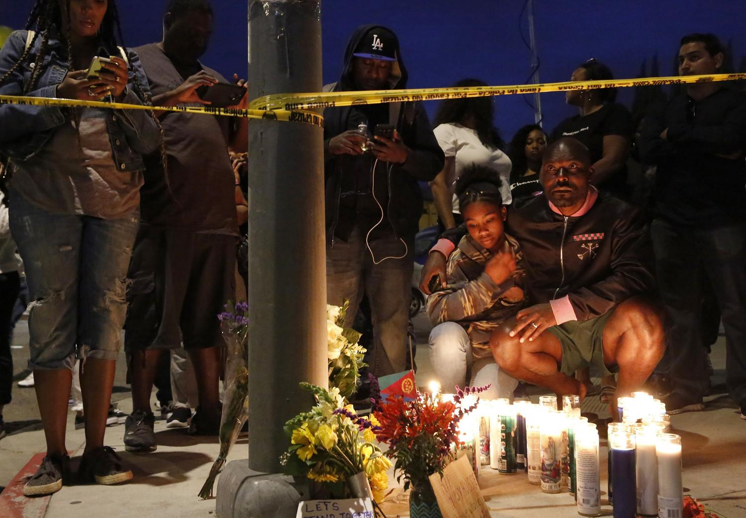 Haitian-French actor Jimmy Jean-Louis and his daughter Jasmin, 16, gather around candles set up across from the clothing store of rapper Nipsey Hussle in Los Angeles, on Sunday, March 31, 2019. Hussle, the skilled and respected West Coast rapper who had a decade-long success with mixtapes but hit new heights with his Grammy-nominated major-label debut album in 2018, was killed at the age of 33.