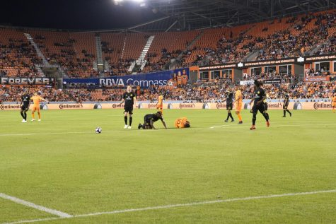 Dynamo player Tomas Martinez shaken up on the play falls down on the field.