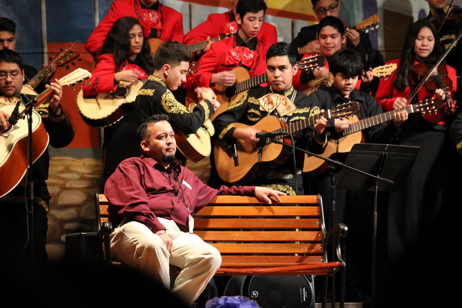 Mariachi instructor Jose Longoria sits on stage as he listens to his students perform on stage at the Sam Houston Math, Science, & Technology Center