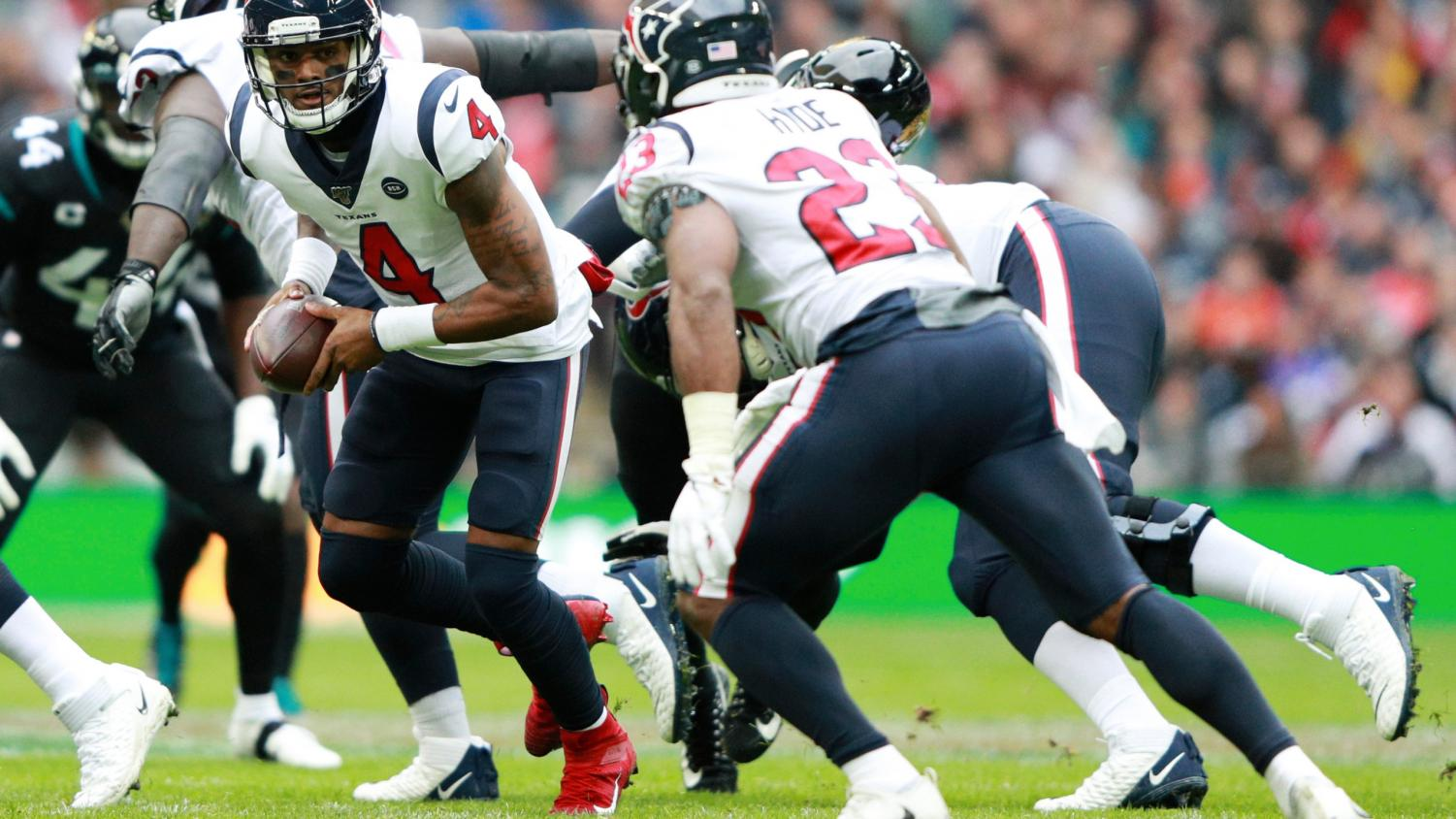 DW4 hands the ball of to Carlos Hyde during yesterday's game at Wembley Stadium.