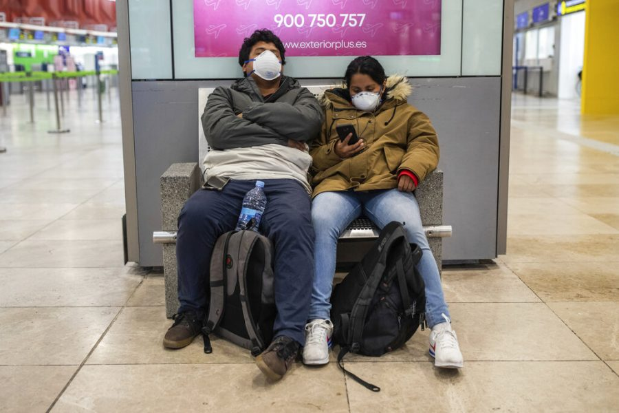 Peruvian passengers wearing protective masks wait at Adolfo Suarez-Barajas international airport on the outskirts of Madrid, Spain, Wednesday, March 11, 2020. Spanish authorities closed schools and halted direct flights to and from Italy. Italy is the country with most coronavirus cases in Europe, and Spain this week reported a sharp increase in cases. For most people, the new coronavirus causes only mild or moderate symptoms, such as fever and cough. For some, especially older adults and people with existing health problems, it can cause more severe illness, including pneumonia.